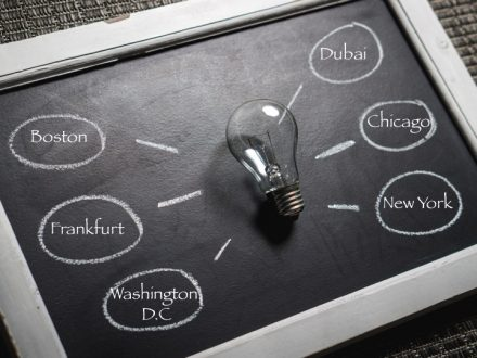 Lightbulb resting on a small chalkboard with the names of international cities surrounding it