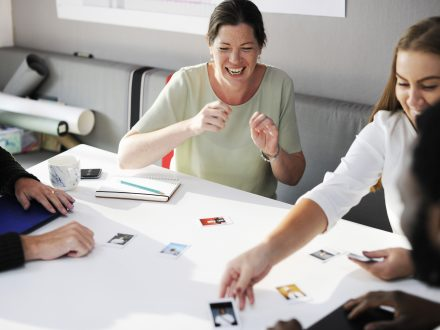 A group of professionals interact at a table; engaging with customers is key in government service design