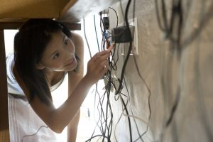 Asian woman looking at plugs under desk