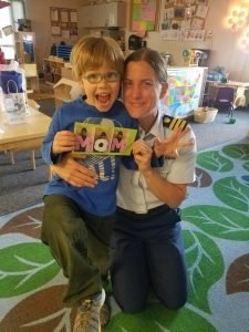 A uniformed Coast Guard woman poses for a photo with her son in his elementary school classroom