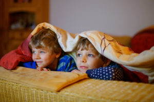 two boys watch TV while snuggling under a blanket