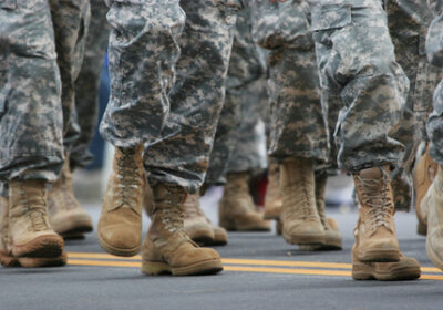 Military service members march on a road. Only boots and lower legs visible