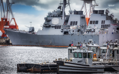 Tugboats wait to assist U.S. a Navy warship in Japan