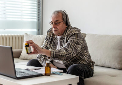 An elderly man consults with a doctor on a virtual medical appointment